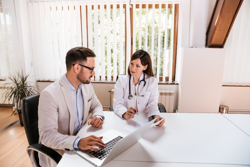 A health care management professional talks with a physician
