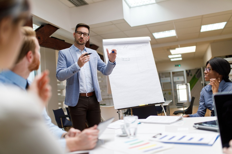 Business man giving a presentation to several people in an office setting
