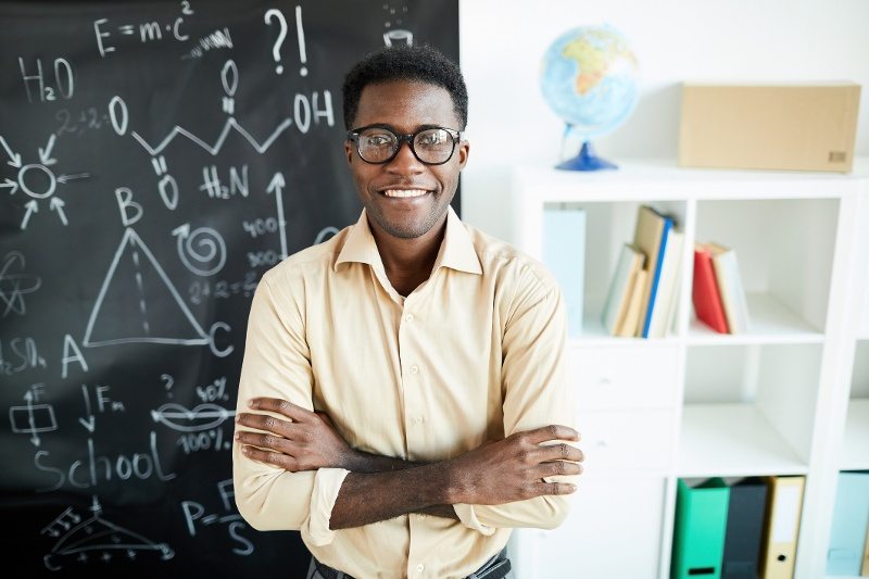 Young teacher in front of a black board